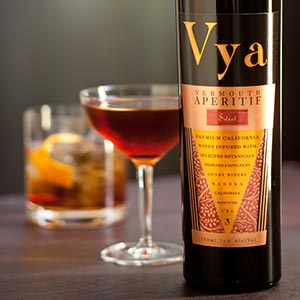 Bottle of Vya Sweet Vermouth in front of two sweet vermouth cocktails.