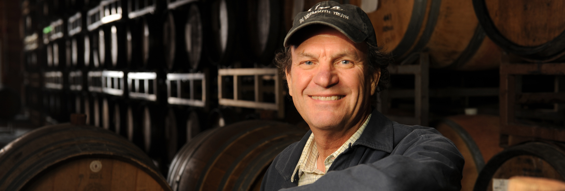 Andrew Quady standing in front of wine barrels