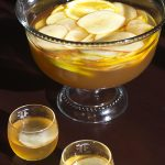 Punch bowl filled with apple slices and pumpkin punch next to a glass of punch and ice.