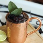 Vya Western Sage Mule cocktail in a mule glass garnished with blackberries.