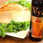 Slices of Vya Sweet Vermouth brined turkey next to a bottle of Vya Sweet Vermouth.
