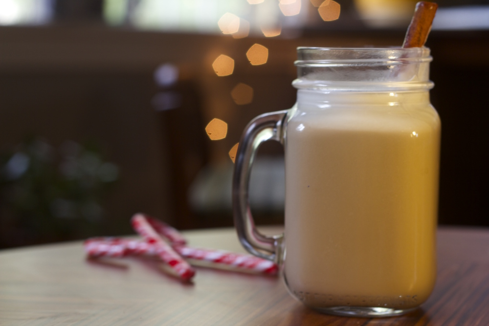 Glass of Vya Egg Nog with a cinnamon stick sticking out, next to a couple of candy canes with lights and Christmas decorations in that background.