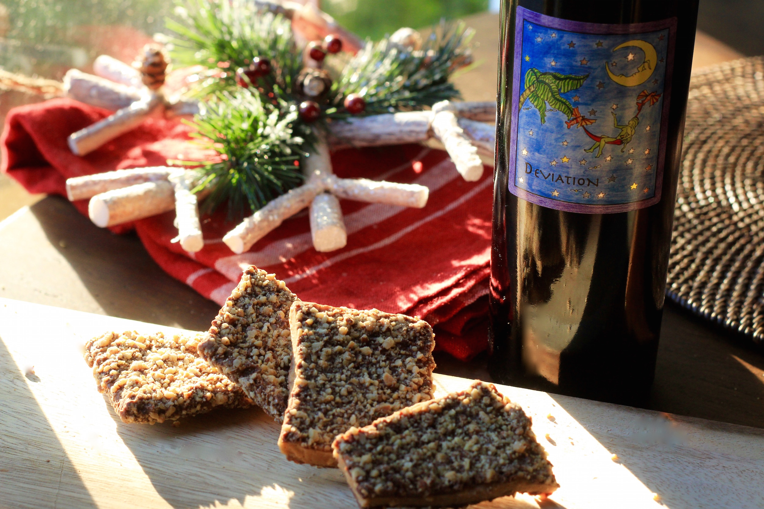 Pieces of English Almond Toffee on a table next to a bottle of Deviation Dessert Wine and Various Christmas Decor