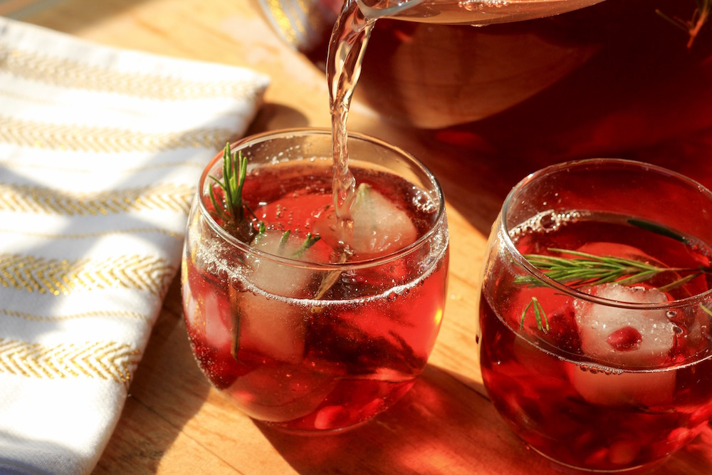 Pitcher of Jingle Juice cocktail being poured into two glasses full of ice, pomegranates and fresh herbs.