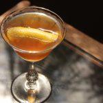 Wild tea cocktail in a glass with an orange peel garnish.