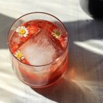 Low proof cocktail with a large ice cube and small edible flowers inside.