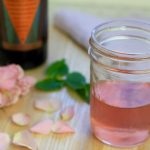Mason jar filled with rose petal infused Vya Whisper Dry Vermouth next to a bottle of Vya Whisper Dry Vermouth and pink roses.