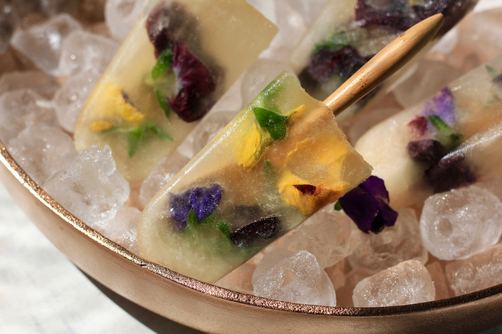 Electra Moscato pops filled with edible flowers in a bowl of ice.
