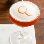Negroni flip cocktail in a coupe glass with a Q written in the egg white topping.