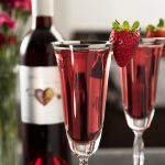 Two champagne flutes filled with sparkling Elysium Black Muscat dessert wine and strawberry garnishes with a bottle of Elysium and flowers in the background.
