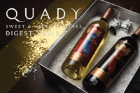 Cover page for 2018 Quady Winery Newsletter: A bottle of Electra Moscato and Red Electra Moscato lying down in a gift box on a table.