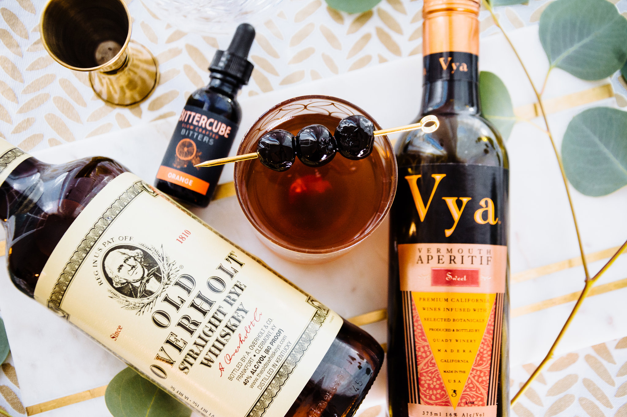 Bottle of Vya Sweet Vermouth, Bittercube bitters and Old Overholt Rye Whiskey lying on a table next to a Manhattan cocktail with maraschino cherry garnish.