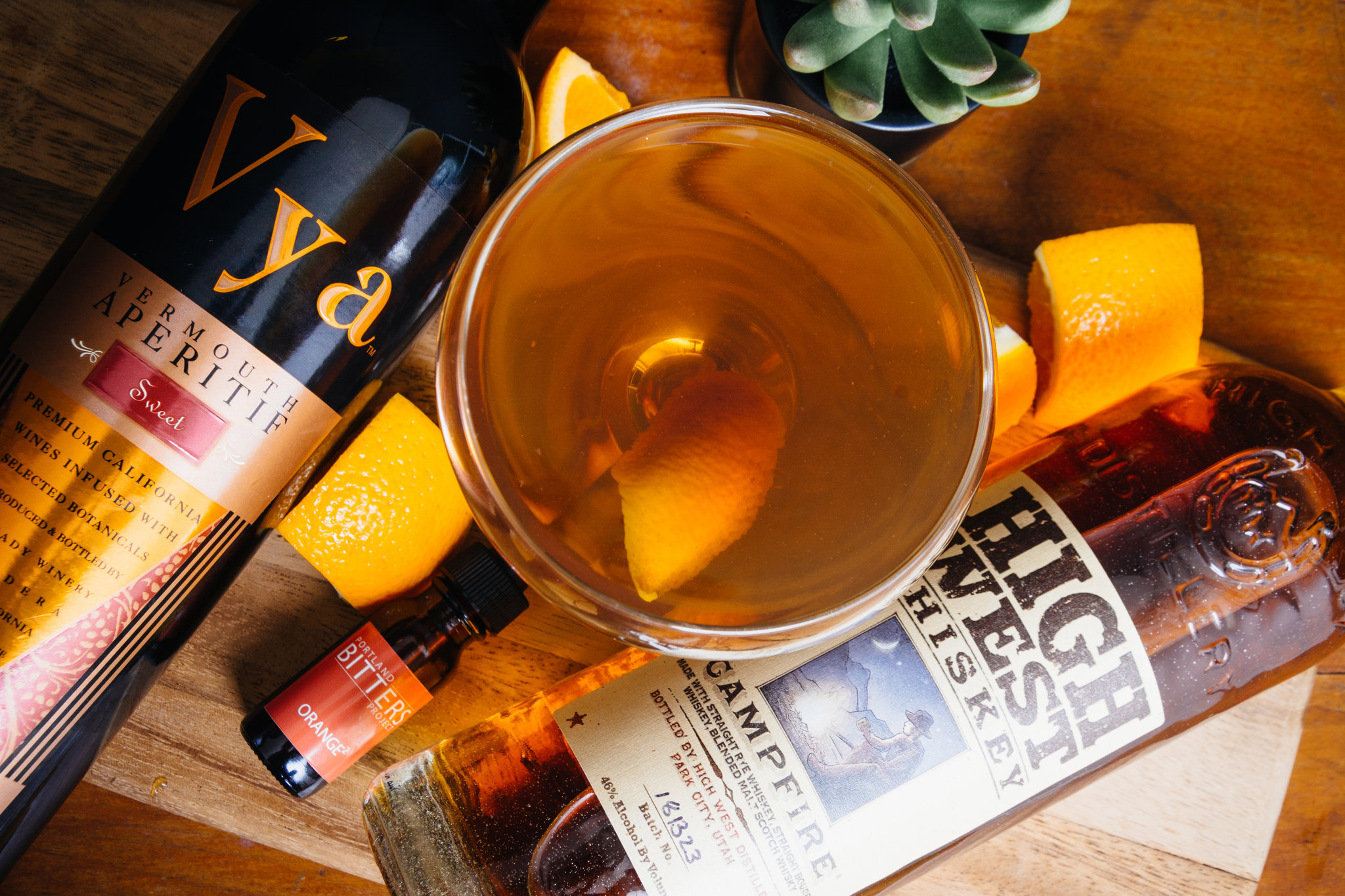Friends and neighbors manhattan cocktail made with High West Campfire Whiskey and Vya Sweet Vermouth in a coupe glass with an orange peel garnish on a table next to a bottle of Vya Sweet Vermouth, High West Whiskey, Bitters and orange slices.