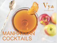Title page for Manhattan cocktail recipe book with a coupe glass filled with a Manhattan cocktail on a table next to apples and stir spoon.
