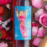 A close up of the new Electra Moscato Rosé surrounded by flowers, roses, fresh strawberries and melon.