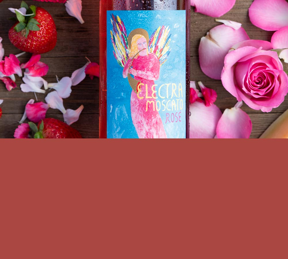 Mobile header image close up of the new Electra Moscato Rosé surrounded by flowers, roses, strawberries and melon.