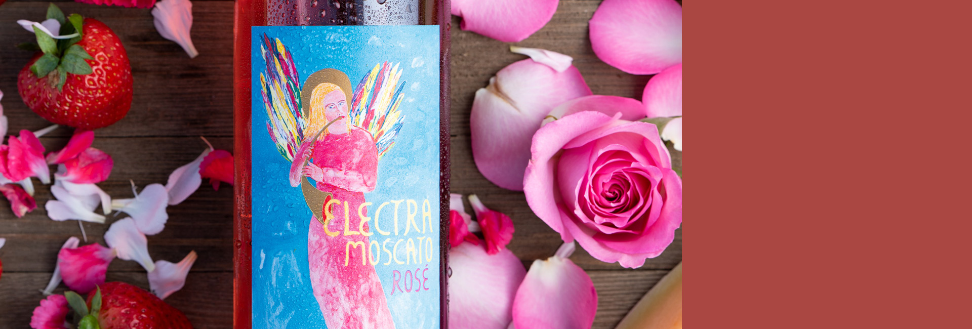 Header image close up of the new Electra Moscato Rosé surrounded by flowers, roses, strawberries and melon.