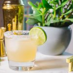 Essensia Margarita Cocktail Recipe in glass with lime garnish sitting on a table