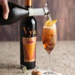 A champagne flute with vya sweet vermouth inside and a bottle of prosecco being poured into it to make the sparkling vya cocktail.