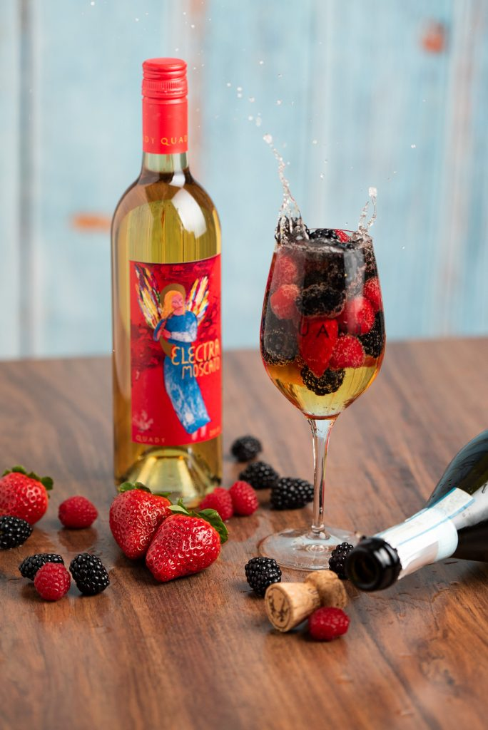 A wine glass filled with Electra Moscato, prosecco and fresh fruit sitting on a table with a bottle of Electra Moscato, some fresh fruit, and an empty bottle of prosecco next to it.