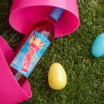 Bottle of Electra Moscato Rosé Wine in a large Easter egg on grass next to smaller Easter eggs.