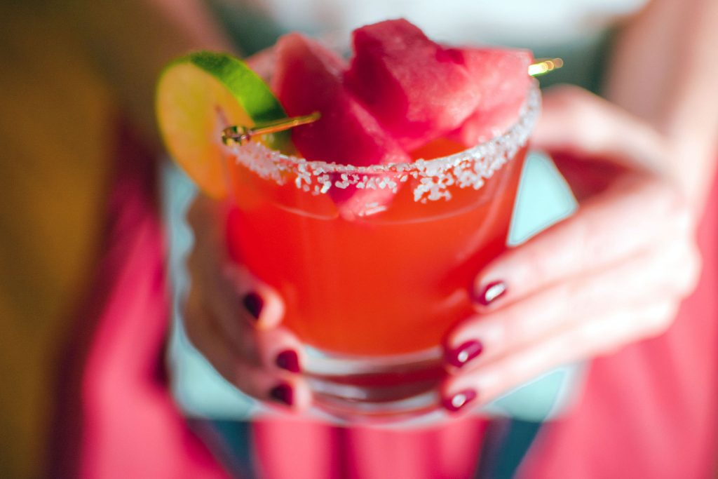 Two hands holding Quady Watermelon Margarita with Red Electra Moscato, Watermelon and tequila in a rocks glass