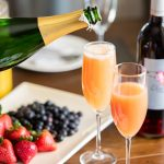 Hand pouring sparkling wine into champagne flute with Elysium black muscat dessert wine and orange juice inside, surrounded by dishes, fruit and a bottle of Elysium.