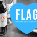 "Black and white photo of Elysium Black Muscat on a table next to fresh fruit with a blue heard graphic and text overlay, ""FLAG, Front Line Appreciation Group."""