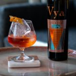 Aperol negroni cocktail created by Beautiful Booze sitting on a coffee table next to a bottle of Vya Whisper Dry Vermouth.