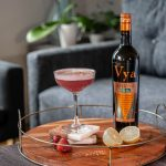 Berry sour cocktail created by Beautiful Booze sitting on a coffee table next to a bottle of Vya Extra Dry Vermouth.