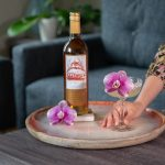 A hand holding a Margarita cocktail created by Beautiful Booze sitting next to a bottle of Quady Essensia Orange Muscat Dessert Wine and an edible orchid flower on a coffee table.