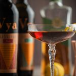 A Perfect Manhattan cocktail in an elegant coupe glass with a lemon peel garnish and bottles of Vya Sweet Vermouth, Vya Extra Dry Vermouth and Rabbit Hole Whiskey in the background.