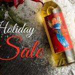 Holiday wine sale banner with a bottle of Electra Moscato lying on a table in snow with a filled wine glass next to it.