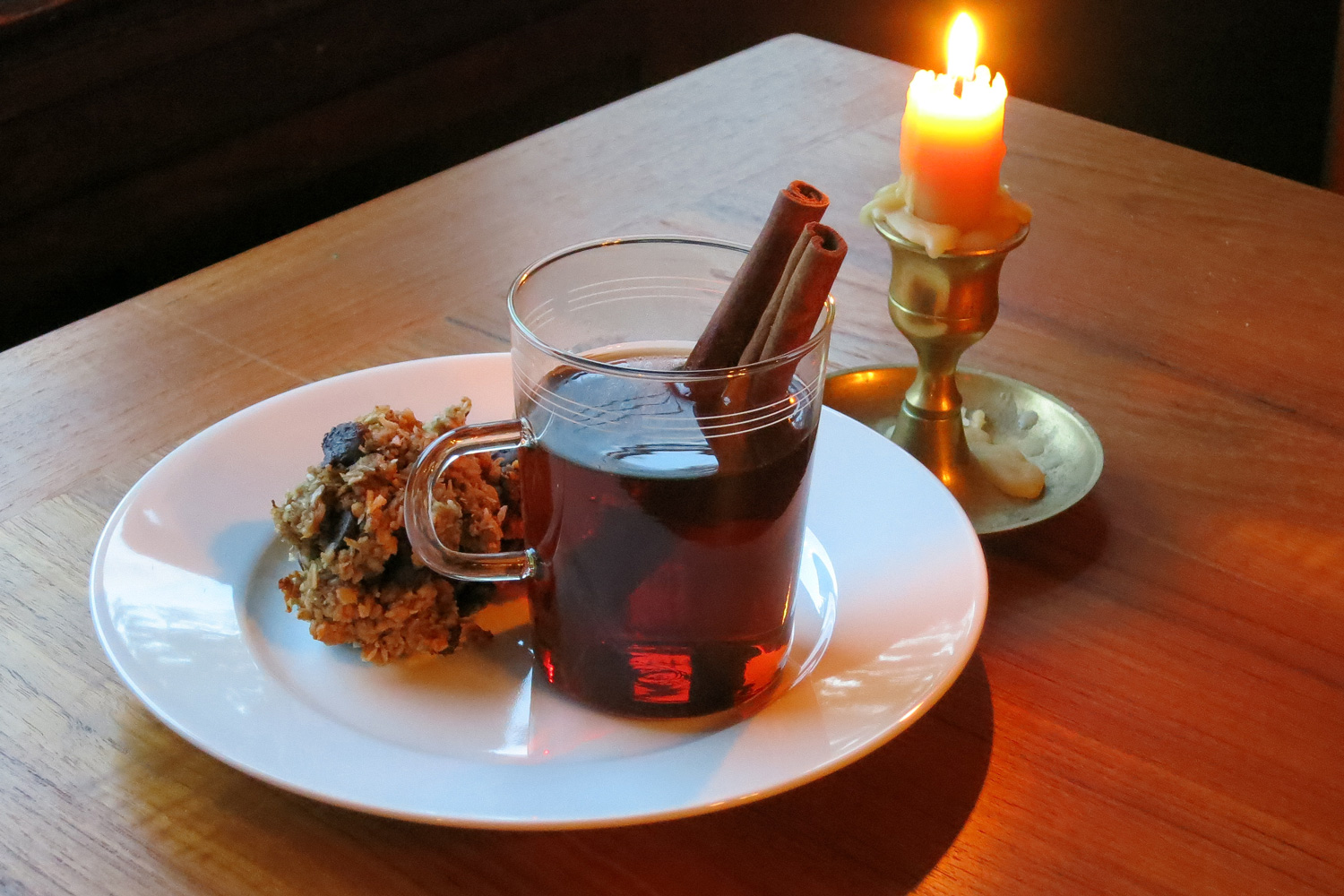 Mug of Mulled Vya winter cocktail with cinnamon sticks, next to a pastry and lit candle.
