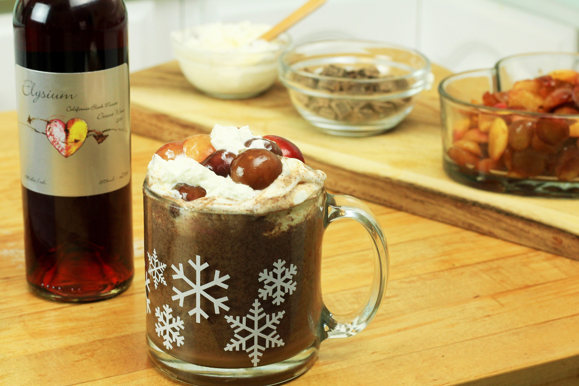 Coffee mug filled with Elysium Hot Chocolate and cherries, next to a bottle of Elysium Black Muscat Dessert Wine and various ingredients.