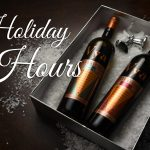 "A bottle of Vya Sweet Vermouth and Vya Extra Dry Vermouth lying down in a gift box on snow with text next to them, ""Holiday Hours."""