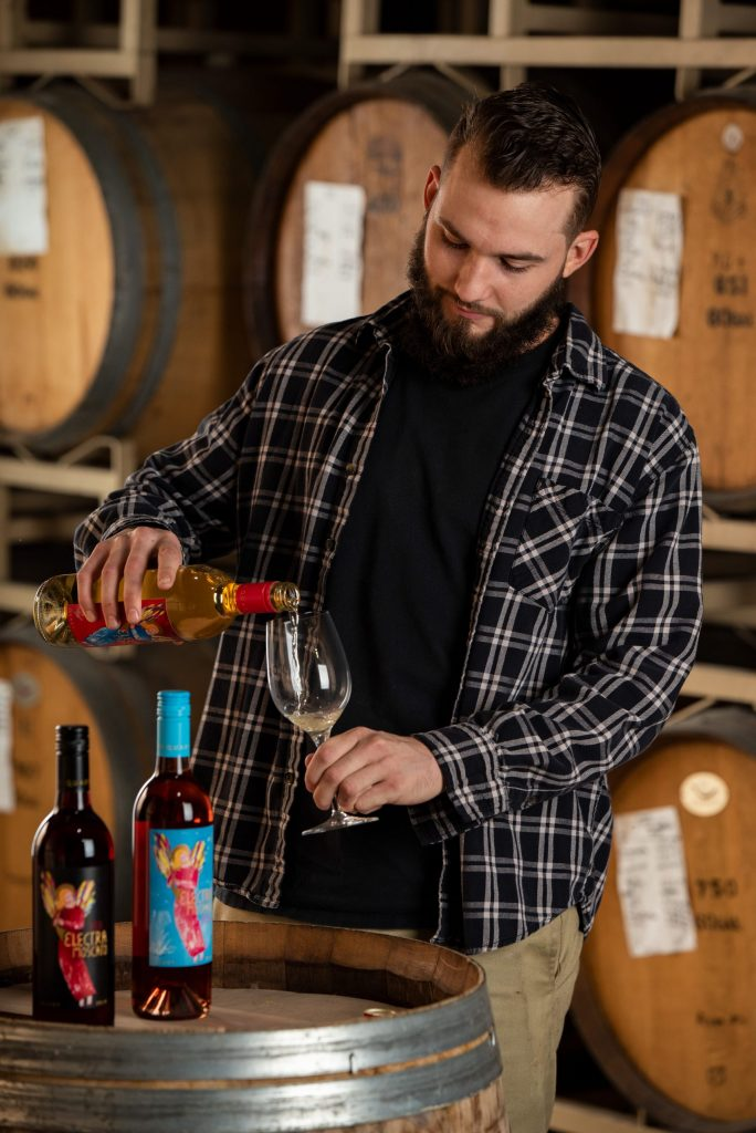 Evan Collins, Laboratory Tech. at Quady Winery, pouring Electra Moscato wine into a wine glass.