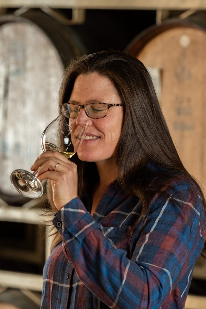 Allie Quady, Health, Safety and Organization Manager at Quady Winery, sipping a glass of Electra Moscato wine.