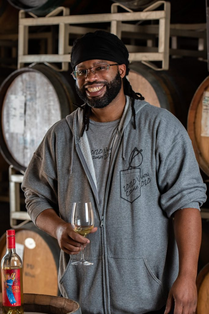 Ja'mal Nelson, General Winery Worker, holding a glass of Electra Moscato wine next to a wine barrel.