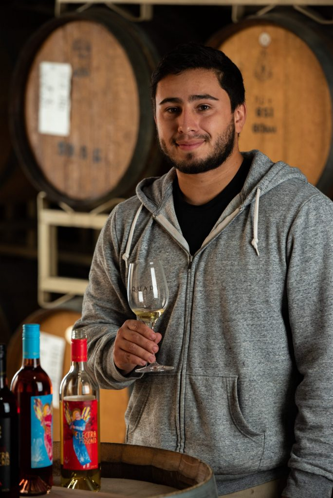 Hector Martinez, General Winery Worker at Quady Winery, holding a glass of Electra Moscato.