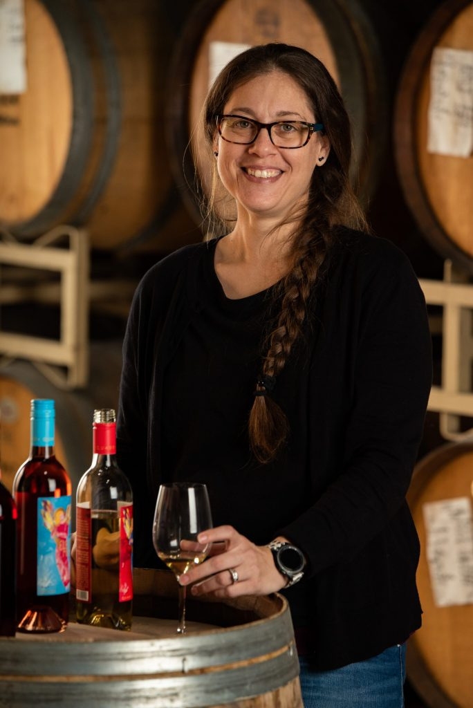 Andrea Milliorn, Senior Accountant at Quady Winery, holding a glass of Electra Moscato while resting on a wine barrel.