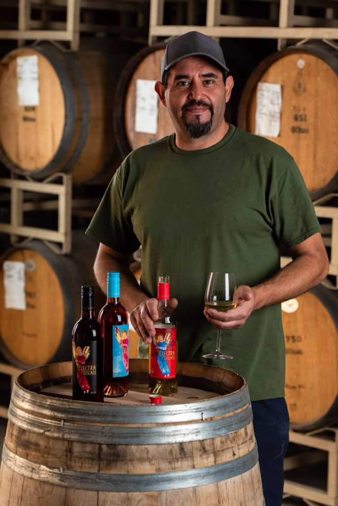 Daniel Martinez, General Winery Worker, holding a glass and bottle of Electra Moscato wine.