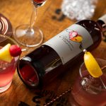 Elysium Black Muscat Dessert Wine lying on a barrel next to cocktails.