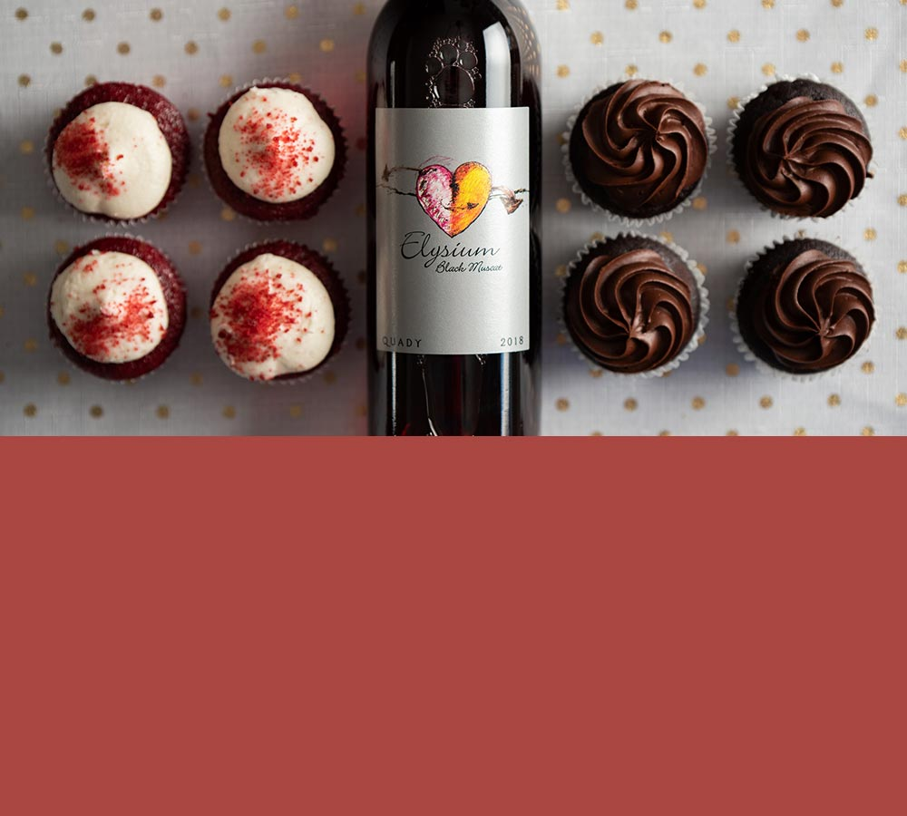A bottle of Elysium Black Muscat dessert wine lying on a table with cupcakes on both sides of it.
