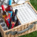Three wine bottles sitting in a picnic basket with four glasses inside. The basket is sitting on top of grass.