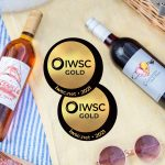 Two gold medals from the International Wine and Spirit Competition next to bottles of Essensia Orange Muscat dessert wine and Elysium Black Muscat dessert wine.