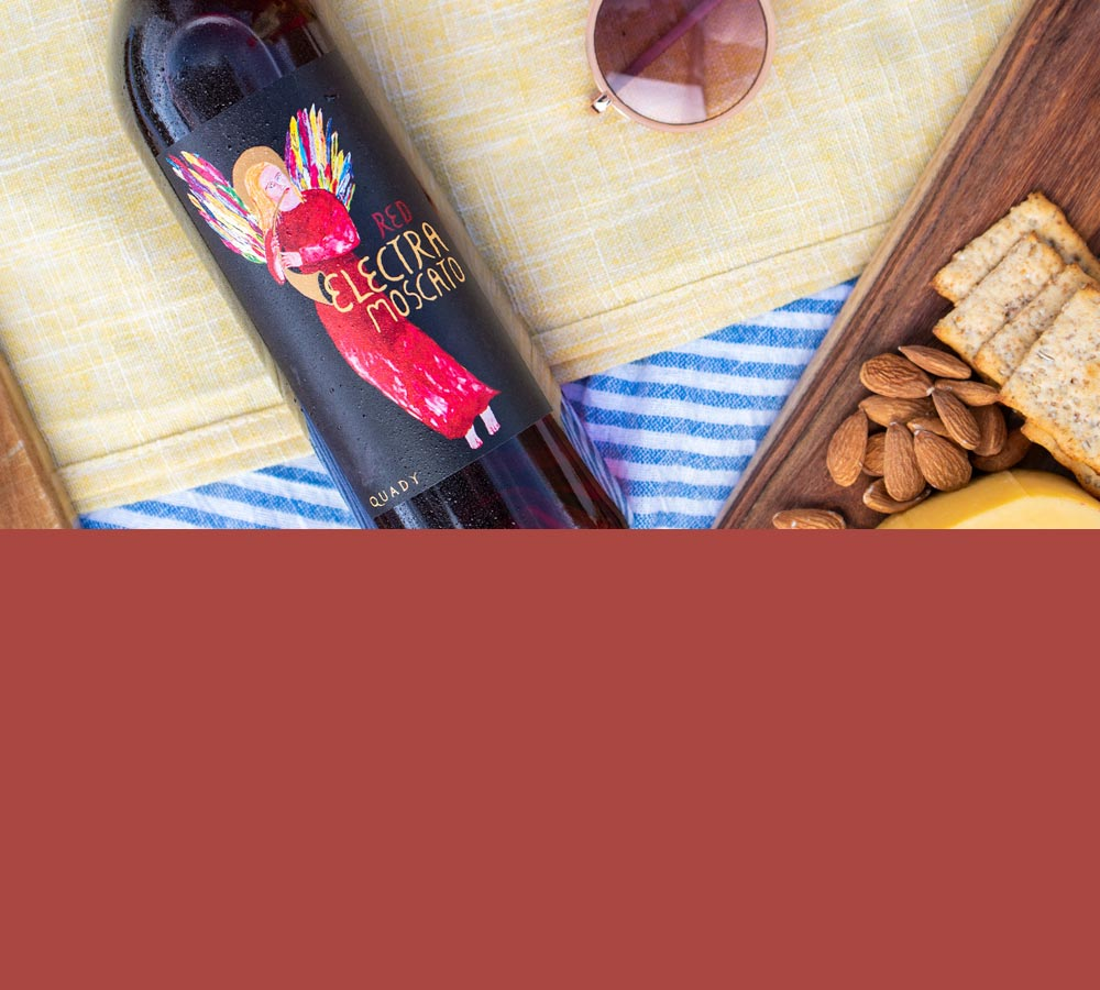 Bottle of Red Electra Moscato wine lying down on a picnic blanket.