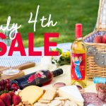 """Picnic setting with bottles of Electra Moscato and text overlay, """"4th of July Sale."""""""