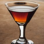 A Manhattan cocktail with vya vermouth sitting on a brown table