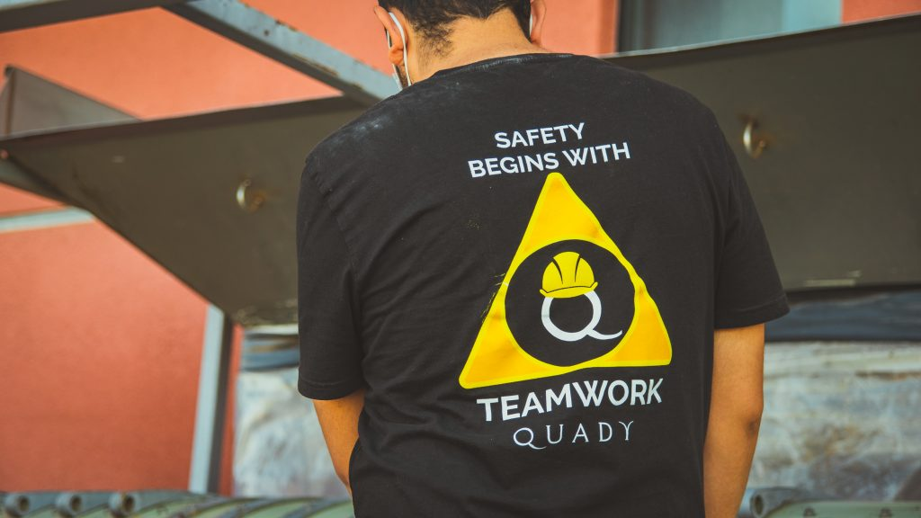 Quady crew member wearing safety shirt standing in front of a machine